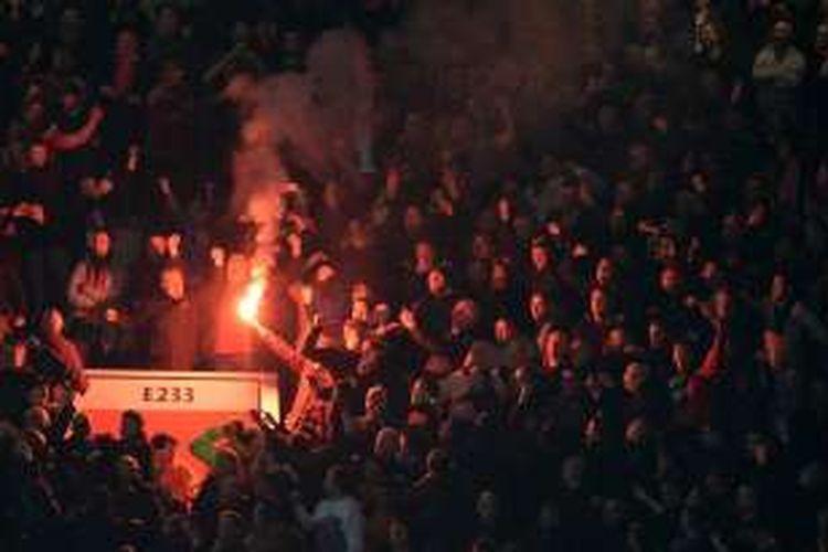 Suporter Liverpool menyalakan flare pada laga kontra Manchester United di Stadion Old Trafford, Kamis (17/3/2016).