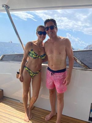 Lara Spencer memamerkan kakinya yang panjang dan kulit cokelat keemasan sembari memeluk suaminya yang mengenakan celana pendek berwarna pink.