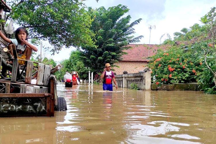 Warga Desa Gondangmanis, Kecamatan Bandar Kedungmulyo, Kabupaten Jombang, Jawa Timur, mengungsi ke kantor desa karena banjir yang melanda tempat tinggal mereka, Jumat (5/2/2021).