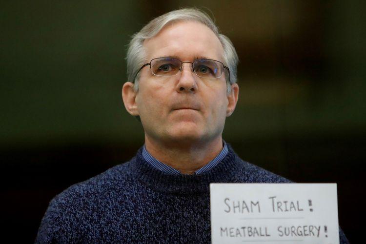Eks marinir AS Paul Whelan (50), dihukum penjara 16 tahun atas tuduhan spionase. Ia dituduh hendak mencuri data rahasia Rusia dalam sebuah flash disk. Saat persidangan Paul Whelan berdiri di bilik pembela, dengan kertas bertuliskan Pengadilan palsu! dan Operasi hernia!. Foto diambil pada Senin (15/6/2020).