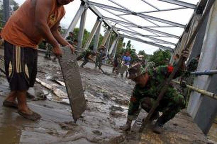 Anggota TNI dari Denzipur membantu warha menyingkirkan lumpur akibat banjir yang menerjang Kota Manado.