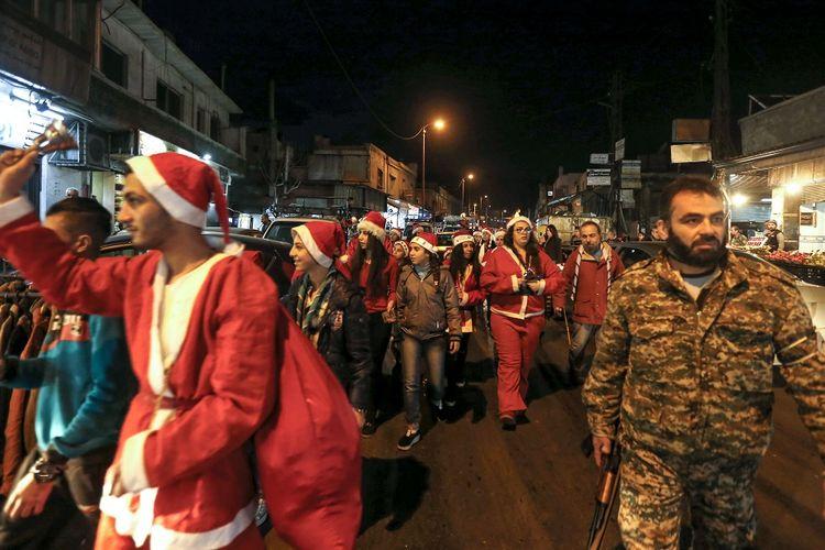 Warga berpakaian seperti Sinterklas berpawai di jalanan ibu kota Damaskus karena merayakan Malam Natal pada Senin (24/12/2018) dengan pengawalan pasukan Suriah.
