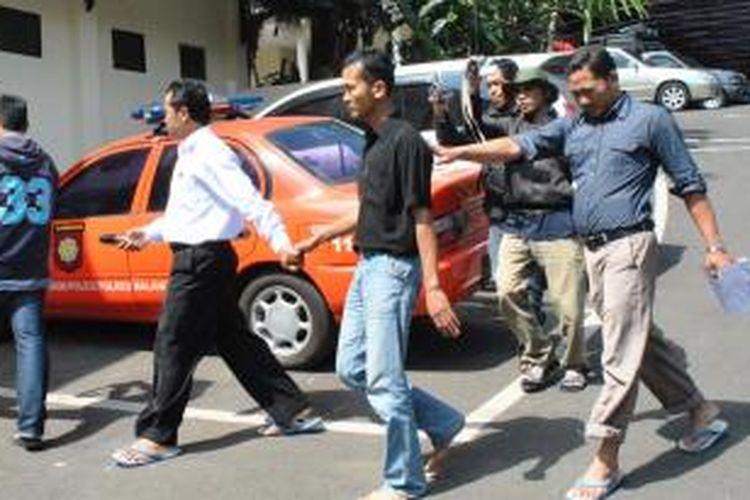 oknum wartawan (Baju warna hitan) di Malang, Jawa Timur, yang diketahui memeras kepala sekolah, saat dibekuk polisi dan digiring ke Mapolresta Malang, Kamis (1/8/2013)