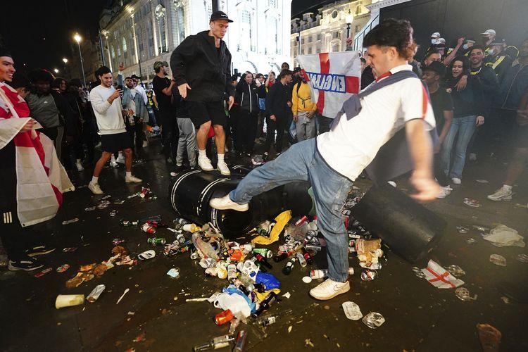 Suporter Inggris menendang dan berdiri di atas tong sampah Piccadilly Circus, London, setelah timnas Inggris kalah melawan Italia dalam final Euro 2020 di Stadion Wembley, Minggu (11/7/2021).