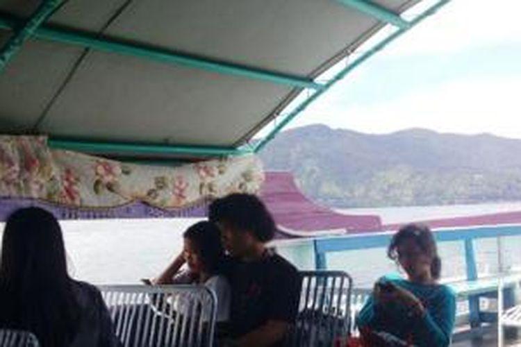 Menikmati penyeberangan ke Pulau Samosir menggunakan kapal wisata.