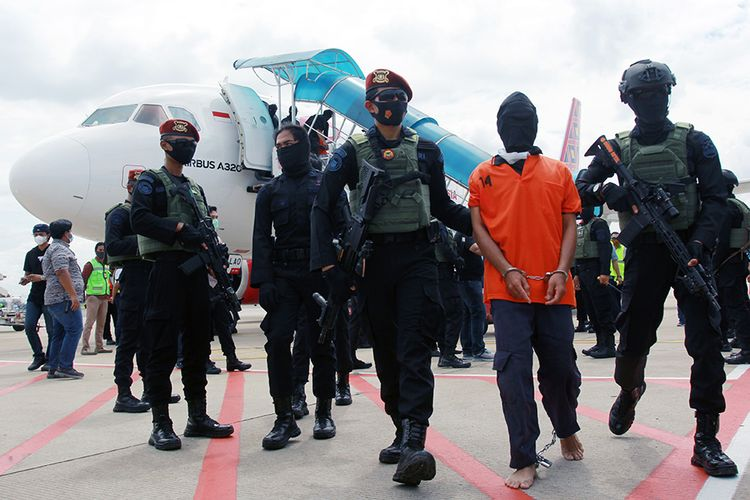 Petugas Detasemen Khusus (Densus) 88 membawa terduga teroris Taufik Bulaga alias Upik Lawanga dari Lampung setibanya di Bandara Soekarno Hatta, Tangerang, Banten, Rabu (16/12/2020). Upik Lawangan merupakan DPO Kepolisian sejak 14 tahun lalu yang diduga merakit bom, kasus bom di Hotel JW Marriott dan Hotel Ritz-Carlton.