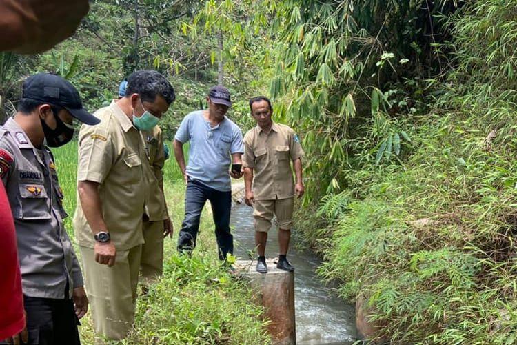 ANGKAT—Seorang anggota polisi dan warga mengangkat jasad Misni, warga Desa Kesugihan, Kecamatan Pulung, Kabupaten Ponorogo yang ditemukan tewas di dalam parit sawah, Selasa (28/9/2021)