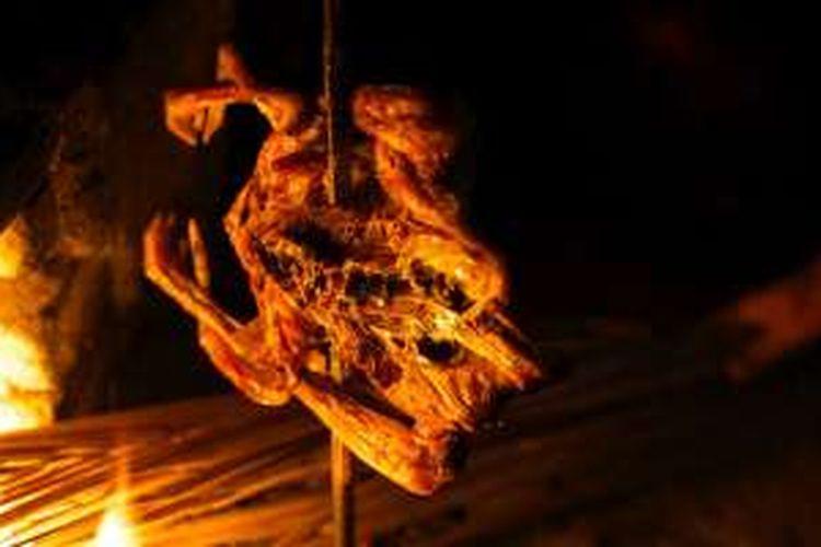 Ayam dibakar sebelum disuwir untuk Pecel Pitik di warung pesantogan Kemangi di Desa Kemiren, Kecamatan Glagah, Banyuwangi, Jawa Timur, Minggu (19/6/2016).
