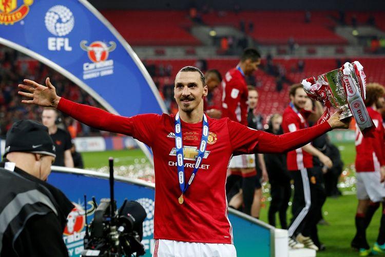 Penyerang Manchester United, Zlatan Ibrahimovic, memegang trofi Piala Liga Inggris setelah tim berjulukan Setan Merah tersebut menang 2-1 atas Southampton pada final di Stadion Wembley, Minggu (26/2/2017).