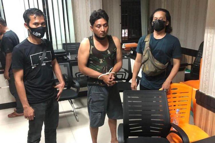 Petugas Ditreskrimum Polda Riau saat mengamankan TS alias Bob (36), DPO pelaku pelemparan potongan kepala anjing ke rumah pejabat Kejati Riau, Kamis (20/5/2021).