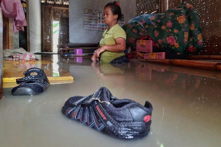 Samen (40) menyelamatkan perabot dari dalam rumah yang terendam banjir akibat luapan Sungai Klawing di Desa Kalialang, Kecamatan Kemangkon, Purbalingga, Jawa Tengah, Kamis (3/12/2020).