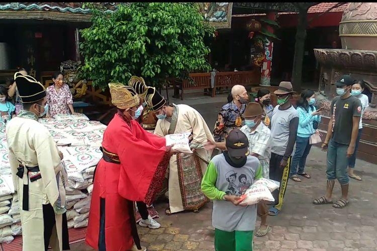 Para umat Konghucu membagikan beras dan angpao kepada warga kuramg mampu dan para tukang becak padai Bulan Ramadhan di Klenteng Kwan Sing Bio, Tuban.