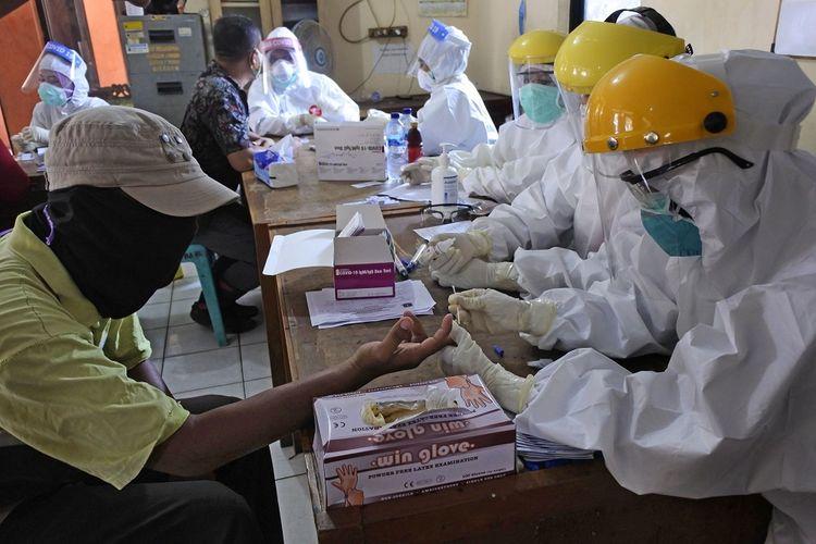 Petugas kesehatan melaksanakan rapid test atau pemeriksaan cepat COVID-19 di Pasar Kranggot, Cilegon, Banten, Kamis (23/4/2020). Pemeriksaan dilakukan terhadap para pedagang dan pengunjung pasar sebagai upaya mencegah penyebaran COVID-19 dari orang-orang yang berpotensi terpapar saat beraktivitas di ruang publik. ANTARA FOTO/Asep Fathulrahman/aww.