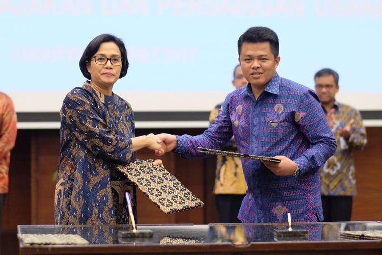 Menkeu Sri Mulyani dan Ketua KPPU Syarkawi Rauf berjabat tangan usai penandatanganan Nota Kesepahaman, Kamis (2/3/2017).