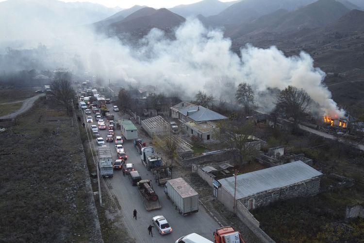 Asap mengepul dari rumah yang terbakar di Nagorno-Karabakh, dan kendaraan terjebak macet di jalan Kaljabar yang menuju Armenia pada Sabtu (14/11/2020). Wilayah itu akan diserahkan ke Azerbaijan sesuai kesepakatan damai untuk mengakhiri perang selama 6 minggu.