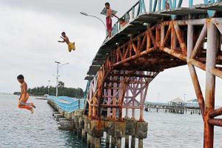 Anak-anak terjun ke laut dari Jembatan Cinta di Pulau Tidung, Kepulauan Seribu, Sabtu (14/3/2015). Jembatan Cinta merupakan salah satu ikon wisata di Pulau Tidung dan salah satu tujuan wisata utama di Kepulauan Seribu.