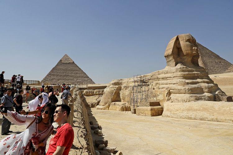Wisatawan berfoto dengan latar belakang patung Spink dan piramida di Mesir.
