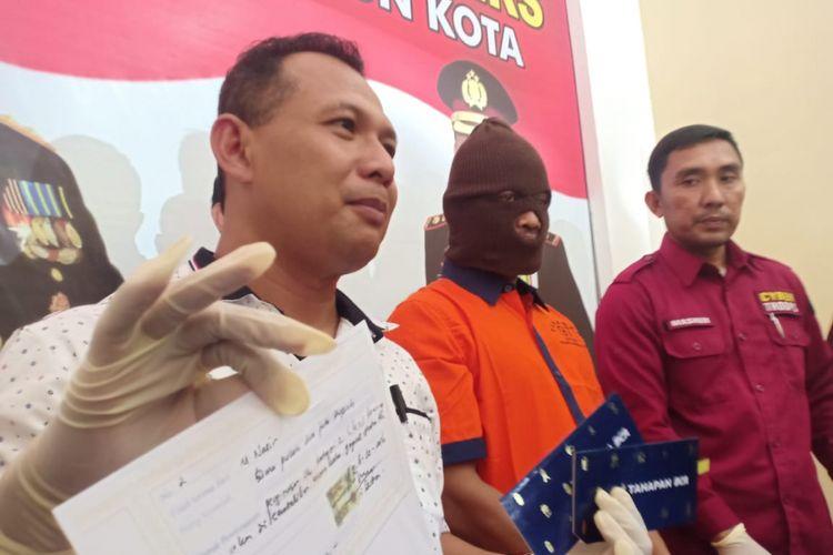 Aparat Polres Madiun Kota menunjukkan barang bukti dan tersangka penipuan berkedok penerimaan CPNS yang menelan korban guru honorer SD di Kota Madiun, Kamis (21/2/2019).