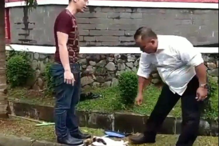 Tangkapan layar video seorang pria berbaju merah diduga tega menyiksa kucing di kawasan Serpong, Tangerang Selatan.