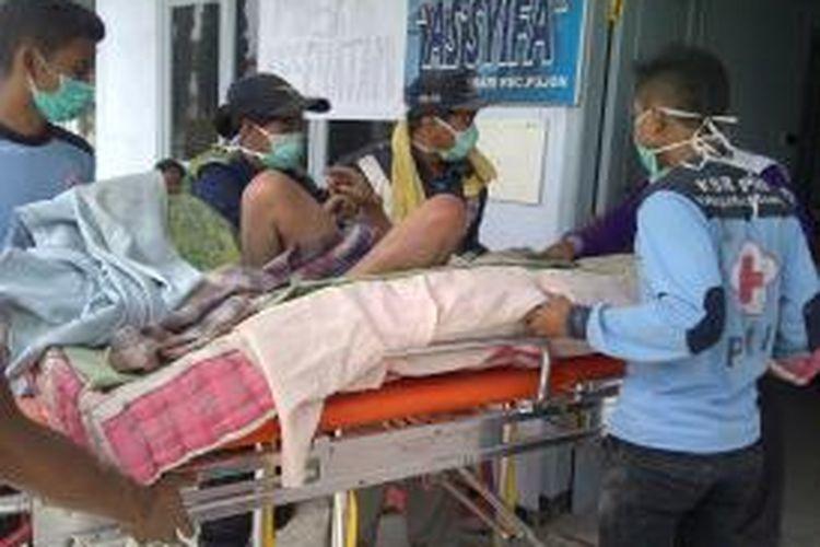 Seorang warga yang sakit saat dibawa ke posko kesehatan yang disediakan di posko pengungsian, di kantor Kecamatan Pujon, Kabupaten Malang. Sabtu (15/2/2014).