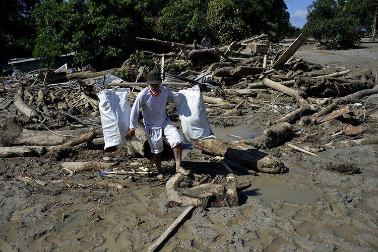 Warga mengangkat barang miliknya melewati material lumpur dan potongan batang pohon di Desa Radda, Kabupaten Luwu Utara, Sulawesi Selatan, Sabtu (18/7/2020). Pascabanjir bandang sejumlah warga yang terdampak mulai mengambil barangnya yang masih bisa digunakan.
