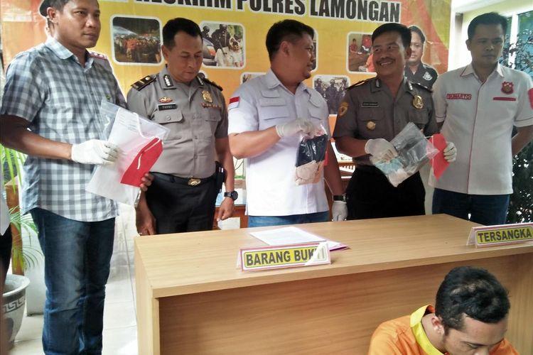 SR duduk tertunduk saat dihadirkan dihadapan awak media dalam rilis di Mapolres Lamongan, Kamis (4/7/2019).