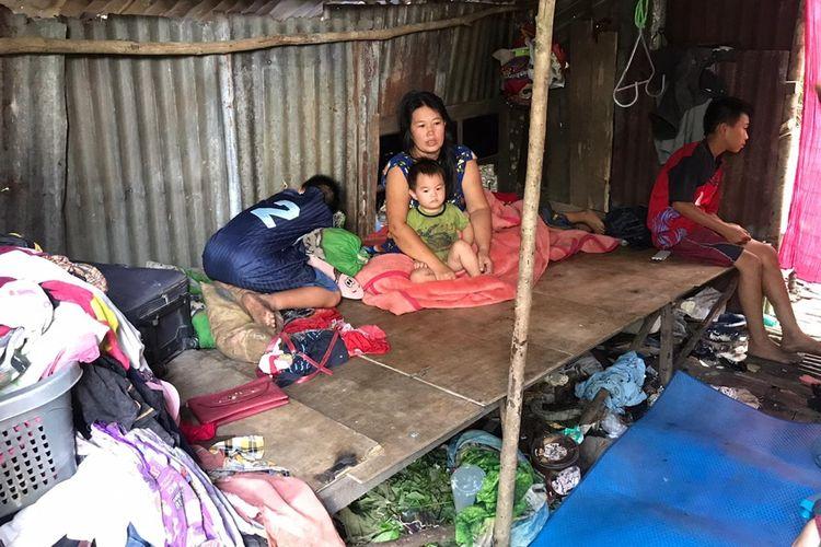 Lena bersama anaknya di gubuk berdinding seng bekas mirip kandang ayam di Jalan Tani, Desa Mega Timur, Kecamatan Sungai Ambawang, Kabupaten Kubu Raya, Kalimantan Barat.(KOMPAS.COM/HENDRA CIPTA)