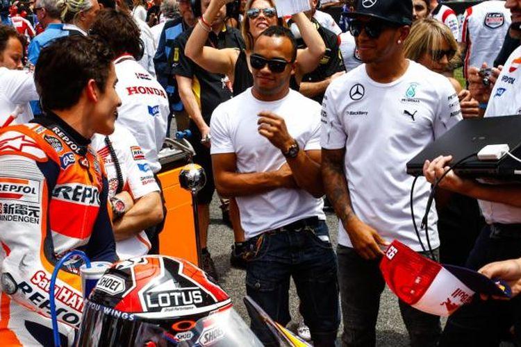 Pebalap Repsol Honda asal Spanyol, Marc Marquez (kiri), berbicara dengan pebalap Formula 1 asal Inggris, Lewis Hamilton (tengah), jelang start GP Catalunya, Minggu (15/6/2014).
