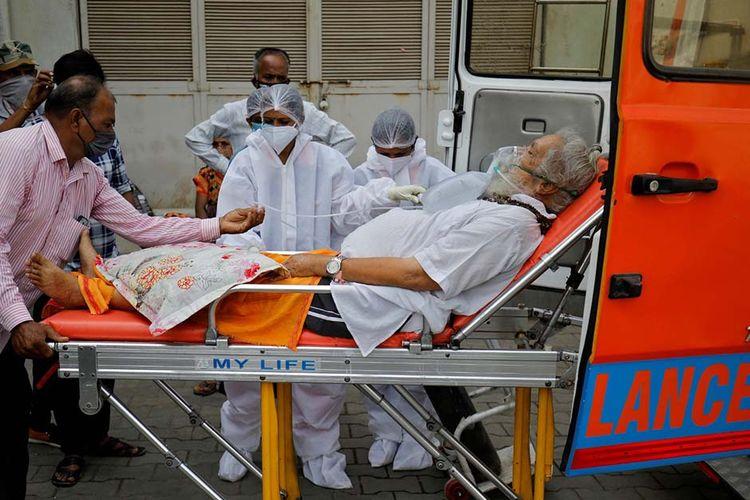 Seorang pasien memakai masker oksigen dibawa ke rumah sakit Covid-19 untuk dirawat di tengah penyebaran penyakit virus corona (Covid-19) di Ahmedabad, India, Senin (26/4/2021). India dihantam kengerian dengan lonjakan kasus Covid-19 mencetak rekor tertinggi dunia melampaui 17 juta kasus.