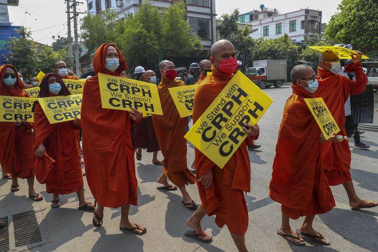 Para biksu Buddha yang mendukung pengunjuk rasa anti-kudeta dengan membawa plakat dengan huruf CRPH yang berarti mendukung Parlemen Myanmar yang digulingkan junta militer di Mandalay, Myanmar pada Rabu 10 Maret 2021.