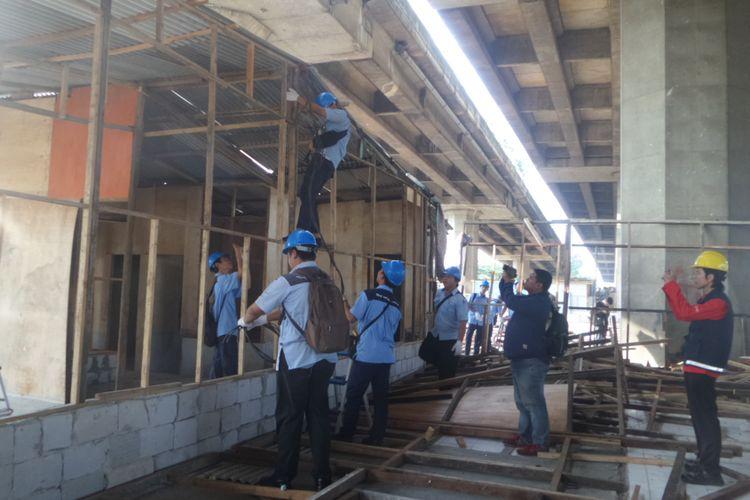 Petugas PLN mencabut aliran listrik yang terpasang di salah satu bangunan semi permanen di bawah kolong tol dekat RPTRA Kalijodo, Rabu (14/6/2017)