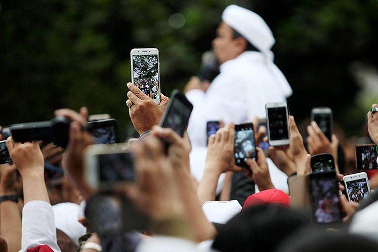 Rekam Rizieq - Massa dari Front Pembela Islam (FPI)  merekam pimpinan FPI Rizieq Syihab saat berbicara kepada pendukungnya di depan Mapolda Jawa Barat, Bandung, Jawa Barat, seusai diperiksa oleh Polda Jabar, Kamis (12/1). Rizieq diperiksa oleh Polda Jabar atas laporan Sukmawati Soekarnoputri tentang penghinaan atas Pancasila sebagi dasar negara.  Kompas/Rony Ariyanto Nugroho (RON) 12-01-2017