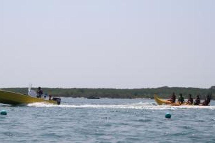 Turis domestik mencoba wahana banana boat di Pantai Tanjung Lesung, Banten.