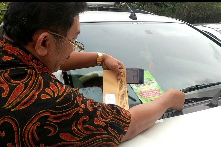 Petugas pajak dari Satuan PKB dan BBNKB Jakarta Utara menempel pemberitahuan tentang tunggakan pajak pada sebuah mobil di tempat parkir Mal Pluit Village, Kamis (12/12/2019) siang.