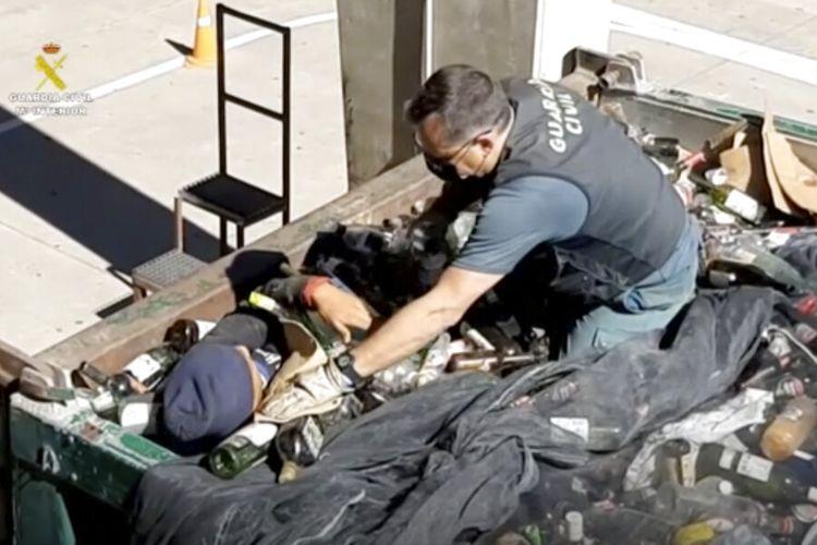 Dalam gambar yang diambil dari video yang disediakan oleh Guardia Civil, seorang petugas dari Guardia Civil membantu seorang pria keluar dari bawah botol kaca dalam sebuah wadah di Melilla, Spanyol, Jumat (19/2/2021).