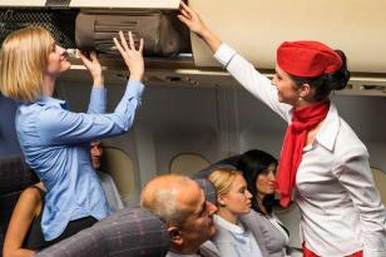 ILUSTRASI - Seorang pramugari menolong penumpang yang membawa bagasi ke kabin pesawat.