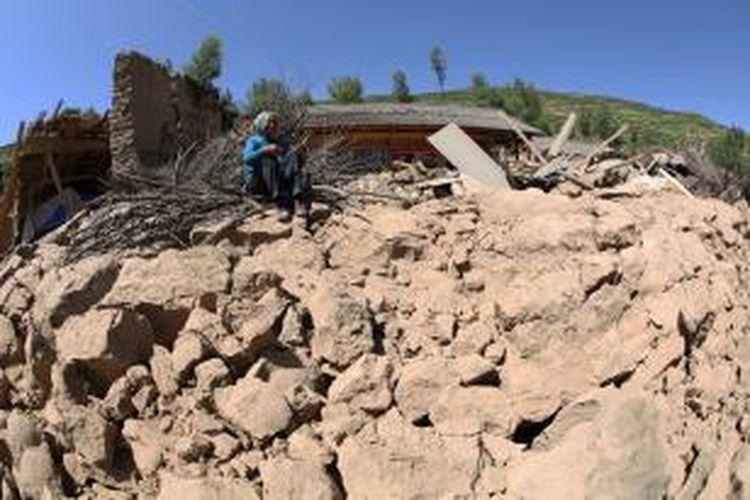 Seorang ibu duduk di samping reruntuhan rumahnya yang luluh lantak akibat gempa berkekuatan 6,6 skala Richter pada Senin (22/7/2013).