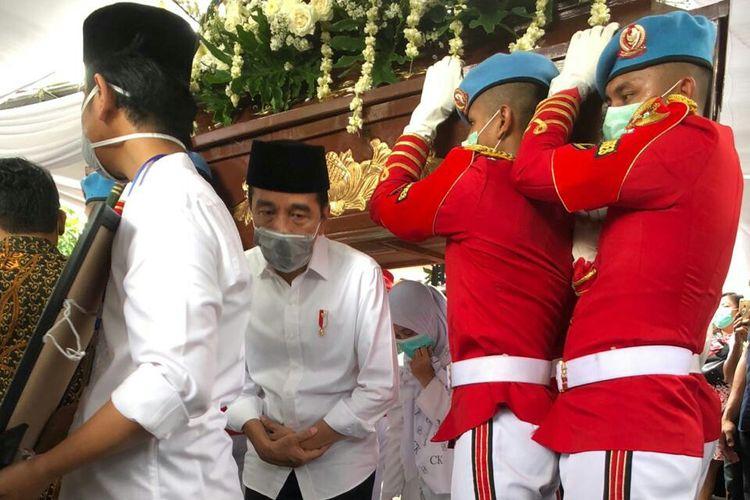 Presiden Joko Widodo melakukan tradisi brobosan di bawah peti jenazah ibundanya