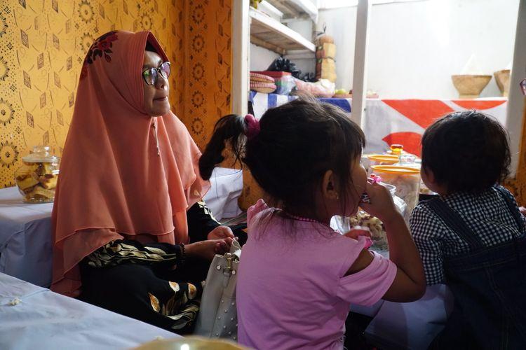 Salah satu anak yang akan menjalani pemotongan rambut gembel, Kayang Ayuningtiyas Nugroho (tengah), didampingi ibunya di rumah Tua Adat Ki Sumanto, di kawasan Dieng, Jawa Tengah, Sabtu (3/8/2019).