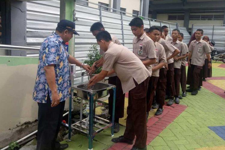 Sejumlah siswa sekolah menengah pertama di Surabaya memanfaatkan wastafel yang disediakan Pemerintah Kota Surabaya untuk cuci tangan, Jumat (6/3/2020).
