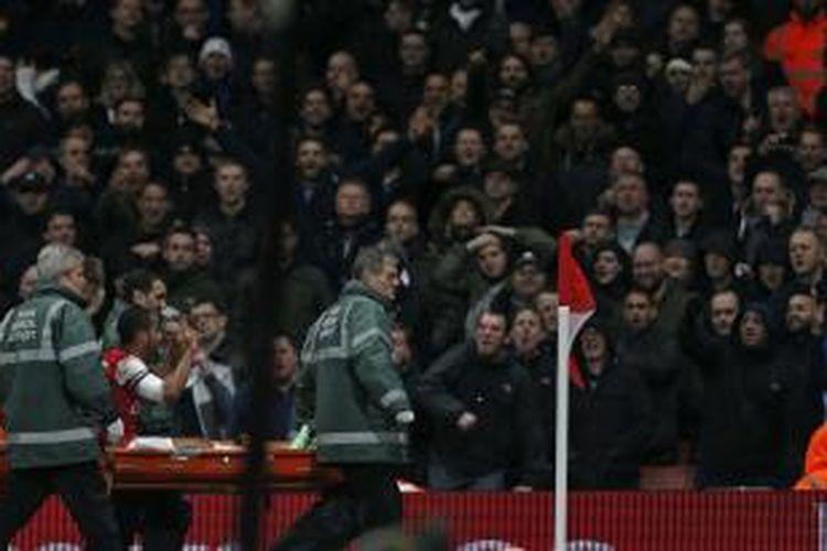 Gelandang Arsenal, Theo Walcott, saat ditandu keluar lapangan karena mengalami cedera dalam laga putaran ketiga Piala FA melawan Tottenham Hotspur, Sabtu (4/1/2014).