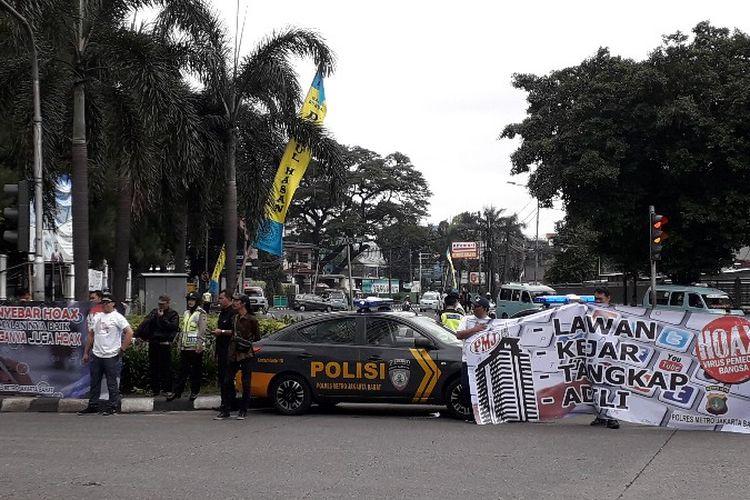 Kepolisian Polres Metro Jakarta Barat membagikan mawar dan stiker sebagai simbol kampanye anti hoaks di jalam S. Supratman, Slipi, Jakarta Barat pada Senin (12/3/2018)