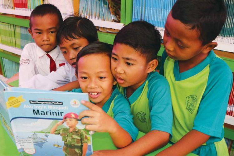Anak-anak sedang membaca di perpustakaan sekolah.