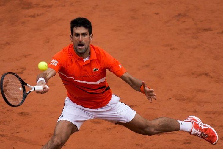 Novak Djokovic mencoba mengembalikan bola pukulan Dominic Thiem pada partai semifinal French Open 2019, 7 Juni 2019.