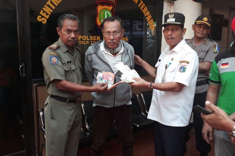 Seorang pria bernama Nazarudin digiring dan dilaporkan ke polisi karena menyebarkan surat palsu untuk meminta tunjangan hari raya (THR) kepada warga di wilayah Kebayoran Lama, Jakarta Selatan, Rabu (6/6/2018).