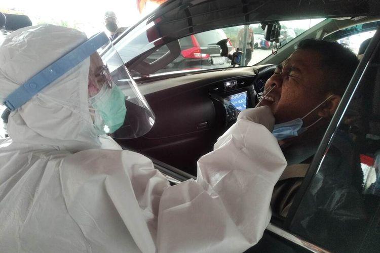 Petugas mengambil sampel dalam proses rapid antigen kepada Masyono, pekerja asal Surakarta yang hendak masuk ke Nganjuk via Exit Tol Begadung, Kamis (7/5/2021).
