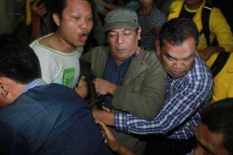 Sastrawan, Sitok Srengenge (tengah, bertopi) usai diperiksa sebagai saksi di Direktorat Reserse Kriminal Umum Polda Metro Jaya, Jakarta Selatan, Rabu (5/3/2014). Sitok diperiksa selama 10 jam sebagai saksi terkait kasus perbuatan tidak menyenangkan yang dilaporkan oleh seorang mahasiswi Universitas Indonesia (UI) berinisial RW. WARTA KOTA/ADHY KELANA
