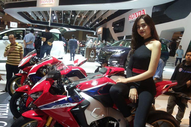Salah soorang sales promotion girl (SPG) berpose di salah satu produk CRF yang dipajang di stan yang dibuka Honda selama Indonesia International Motor Show (IIMS), JIExpo, Kemayoran, Jakarta.