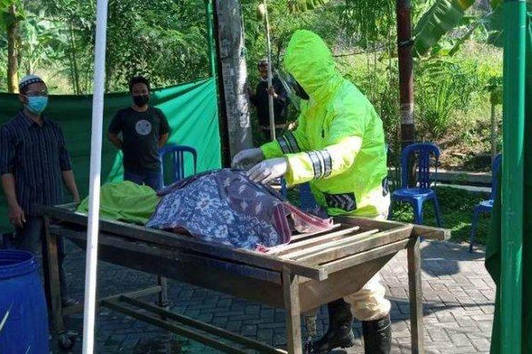 Anggota Polisi Sat Samapta Polrestabes Semarang, Aiptu Andi Surwano memandikan jenazah terpapar Covid-19 di Perum Graha Sendangmulyo Tembalang dengan alat seadanya.
