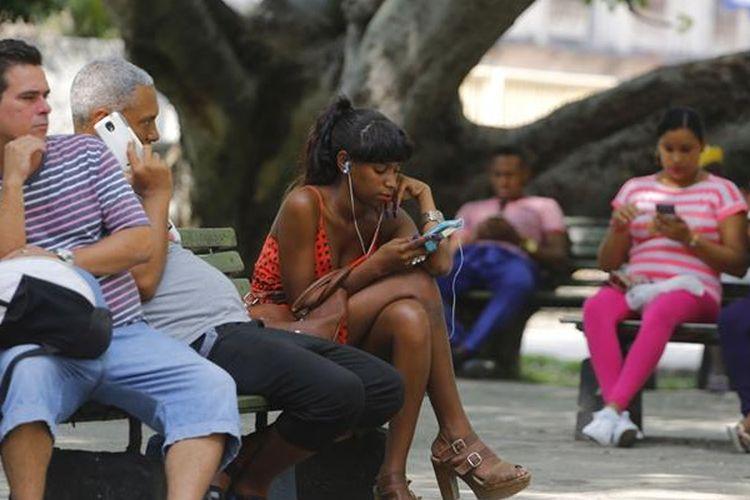 Ilustrasi warga sedang menelepon dan mengakses internet di ponsel mereka.